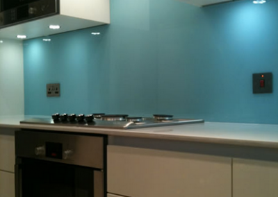 Blue-back-painted-toughen-splashback-in-northern-ireland-with-glass-cut-outs-for-plugs